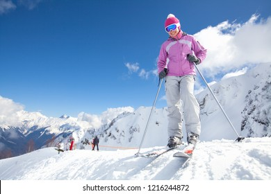 Young woman skiing on a snowy road in the mountains