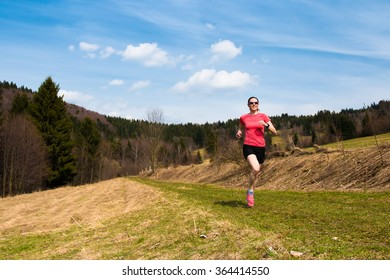 young woman in skirt and glasses jogging on the meadow country side track in the spring