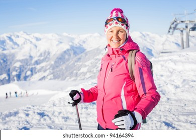 Young woman with skis and a ski outfit in the Zillertal Arena, Austria