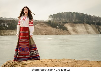 young woman in a Slavic Belarusian national original suit outdoors