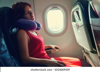young woman sleeping in an airplane seat. traveler in an plane with pillow for neck