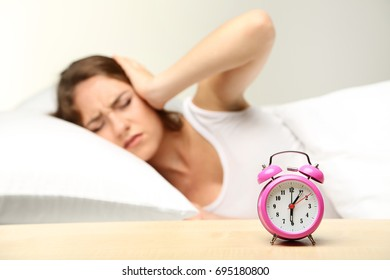 Young woman sleeping in bed with alarm clock