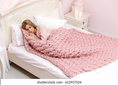 Young woman sleeping in bed with pink merino wool blanket. Plaid of thick yarn. Chunky knit. Pink bedroom.