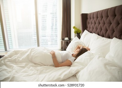 Young woman sleeping comfortably, quality bed linen and bedding, staples quilts and pillows, drank too much the night before, too lazy to shower, having her periods, single woman, overslept