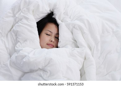 Young woman sleeping, covered by blanket