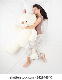 Young woman sleeping in an embrace with a large white teddy bear. Top view photo. Woman with brown hair