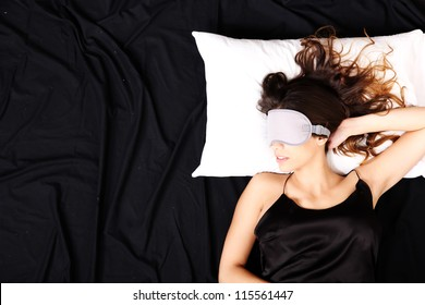 A young woman sleeping with a eye covering mask.