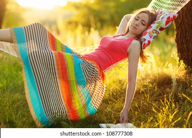 Young woman sleeping in a hammock in garden