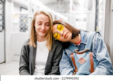 Young woman sleeping on the shoulder of her girl friend in the metro train, friendship and sleepless concept