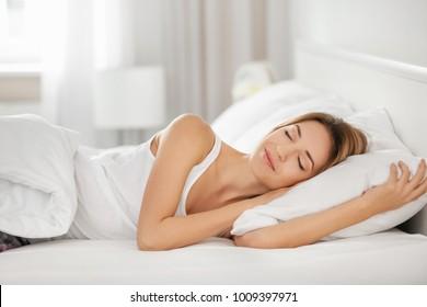 Jonge vrouw slapen op wit kussen in bed