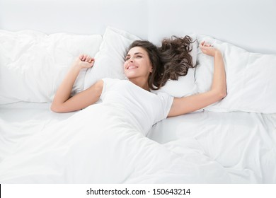 young woman sleeping on the white linen in bed at home, top view