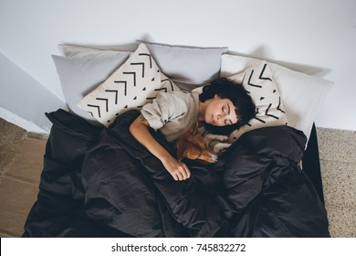 Young woman sleeps in bed, in clean and white simple bedroom, with her best friend, basenji breed puppy dog sleeping next to her, on top of covers. cute and adorable friendship