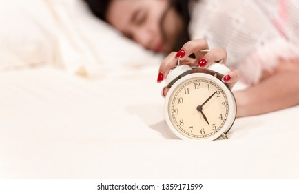 Young woman sleeps in the bed, not wanting to wake up because of the loud alarm clock morning in the holidays.