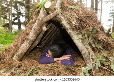 Young woman sleeps in a natural materials survival shelter in the forest
