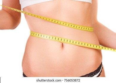 young woman with slim figure measuring a belly size with a measuring tape, isolated