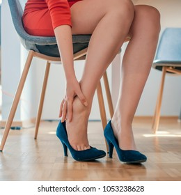 Young woman with slim legs feeling ache because of wearing high heels. Closeup young woman feeling pain in her foot at home. Healthcare and medical concept.