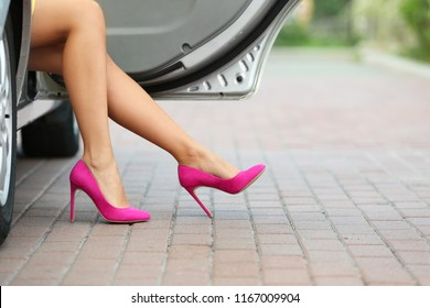 Young woman with slim legs in high heels getting out of car