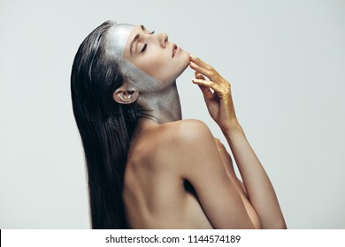 Young woman with sliver colored makeup on face and hands painted in gold standing with her eyes closed. Topless woman in ultra vogue style against grey background.