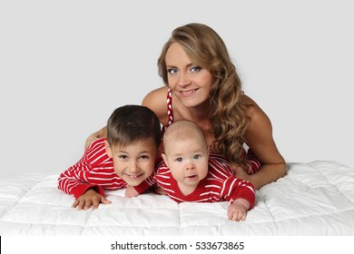 Young woman with small boy and infant baby ob blanket on gray background - Mother and children, motherhood, childcare concept