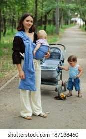 Young woman with a small child in a baby carrier and a toddler standing next to carriage