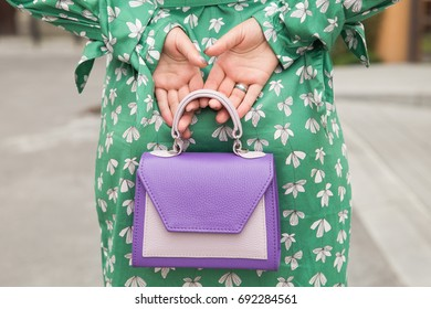 Young woman with a small purple leather handbag. A girl in a silk green dress for a walk in the city. Street fashion look concept, fashionista outfit
