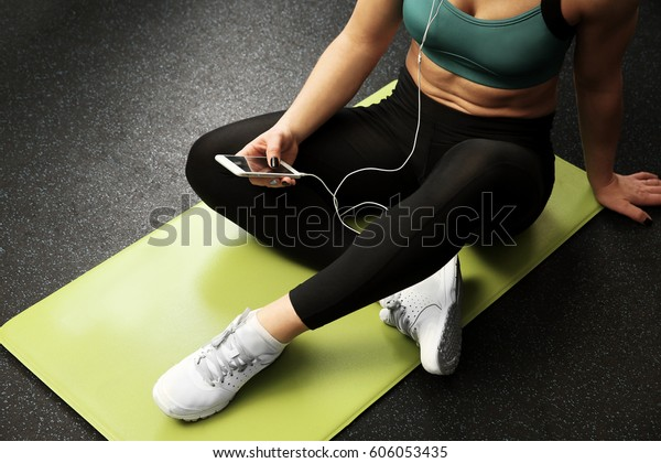 Young woman with smart phone and headphones sitting on mat in a gym