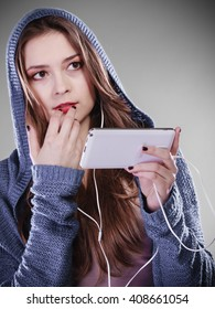 young woman with smart phone listening music. Teen stylish long hair girl in hood relaxing or learning language. Studio shot on gray.
