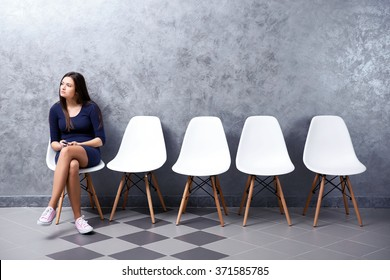 Young woman with smart phone sitting on a chair in grey hall