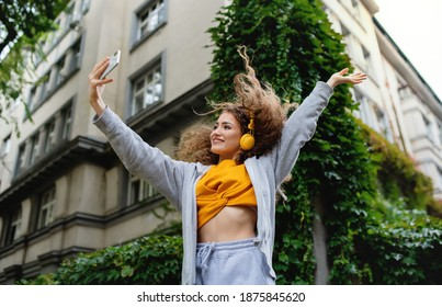 Young woman with smartphone dancing outdoors on street, video for social media concept.