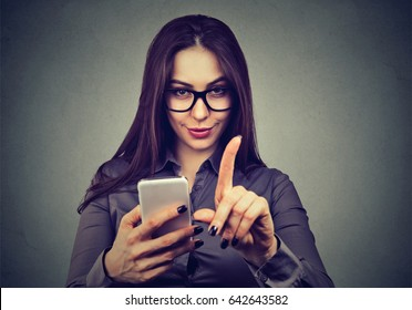 Young woman with smartphone showing no attention with finger hand gesture. Blocking forbidden adult contents, parental control reminder concept