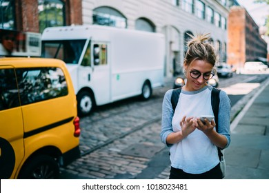 Young woman with smartphone using application for calling taxi online walking on city street,hipster girl satisfied with internet connection sending photos to friend via mobile phone while strolling