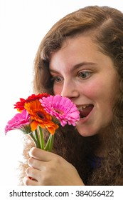 A young woman smelling a bouquet of flowers and laughs
