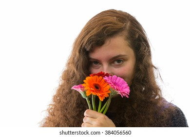 A young woman smelling a bouquet of flowers and smiles