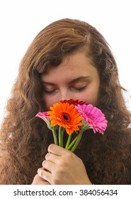 A young woman smelling a flower bouquet with closed eyes and smiles