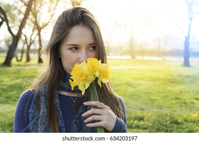 Young woman smelling flowers in nature. Pretty girl holding bouquet of flowers.