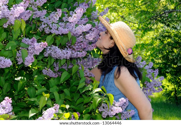 Young Woman Smelling The Perfume From A Lilac Tree