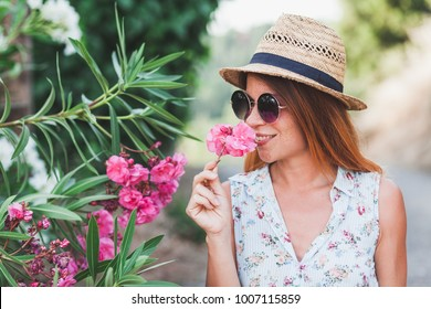 Young woman smelling pink flower in summer
