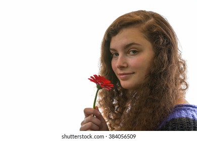 A young woman smelling a red flower and smiles