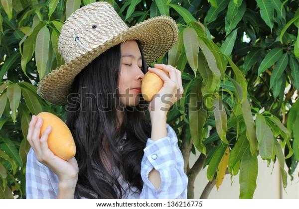 Young woman smelling ripe mango