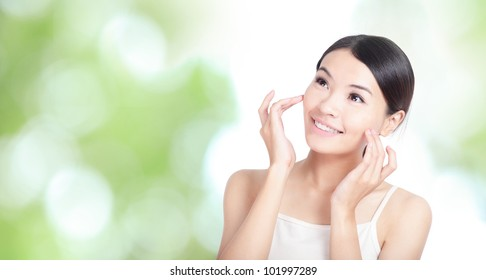 Young woman smile and hand touch face look to up forward concept for health body care with green nature background, model is a asian beauty