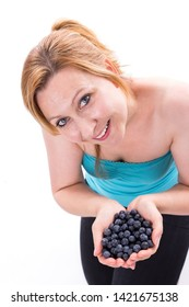 Young woman smiles at the camera and has 2 hands full of blueberries