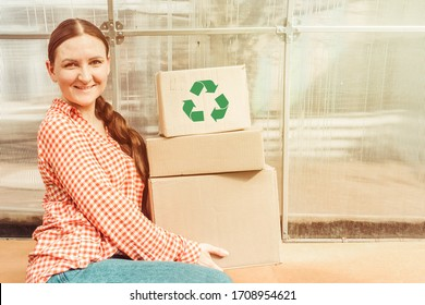 A young woman smiles and holds craft boxes with a recycling icon. Zero waste concept.