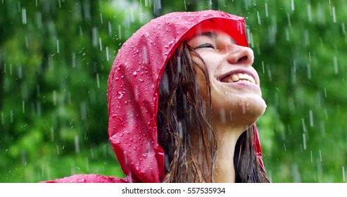 The young woman smiles and laughs under the rain. the rain falls, the drops fall on her face and she is happy with life and nature around. concept of nature and happy life, adventure, purity