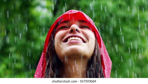 The young woman smiles and laughs under the rain, the rain drops fall on her face and she is happy with life and nature around. concept of nature and happy life,adventure, purity