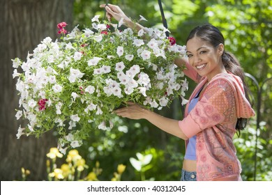 A young woman smiles while posing next to a hanging basket of flowers. Horizontal format.