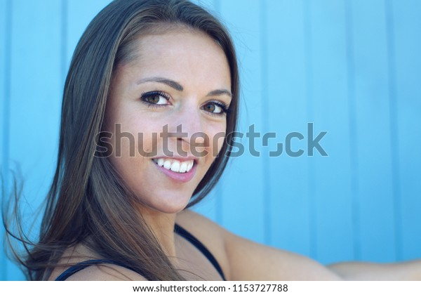 young woman smiling blue background face portrait