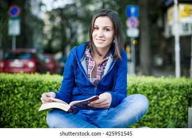 Young woman smiling with a book