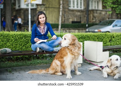 Young woman smiling with a book and two dogs