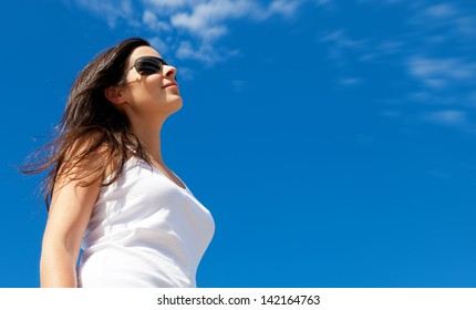 Young Woman Smiling with a Bright Blue Sky Background