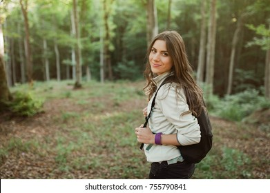 Young woman smiling at camera with backpack in the forest on sunset light in the autumn season, looking up, exploring the nature.